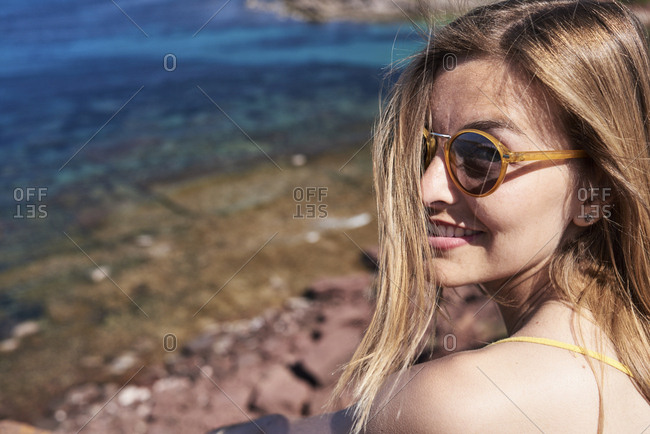Girl in sunglasses smiling at camera over shoulder by the sea