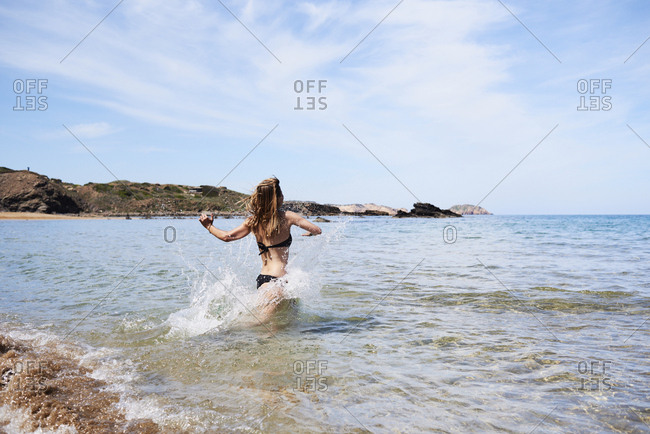 Side view of girl in black bikini running through water in sea