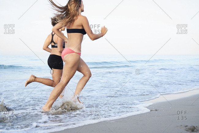Girlfriends workout running at the beach at sunrise
