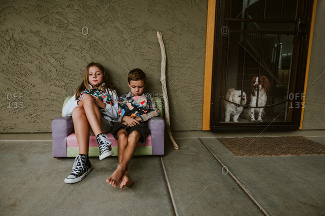 Two kids sitting on couch by front door on porch