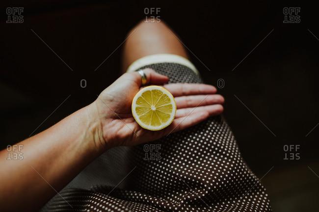 Woman holding a sliced lemon
