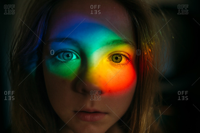 Portrait of a young girl with rainbow glare on her face