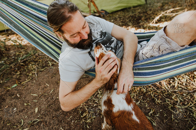 Man resting in hammock petting dog