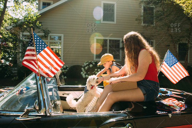 Boy sitting with woman and dog in a convertible on fourth of July