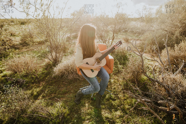 Girl playing guitar on orange chair in the countryside