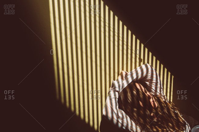 Woman with sunlight shining on her face through blinds