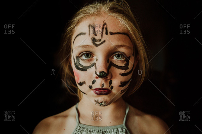 Little girl with bat drawing on face