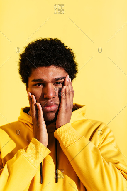 Portrait of a young african man wearing yellow hoodie on yellow wall.