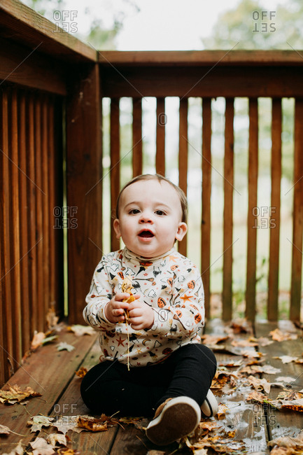 Toddler sitting on deck with fallen leaves