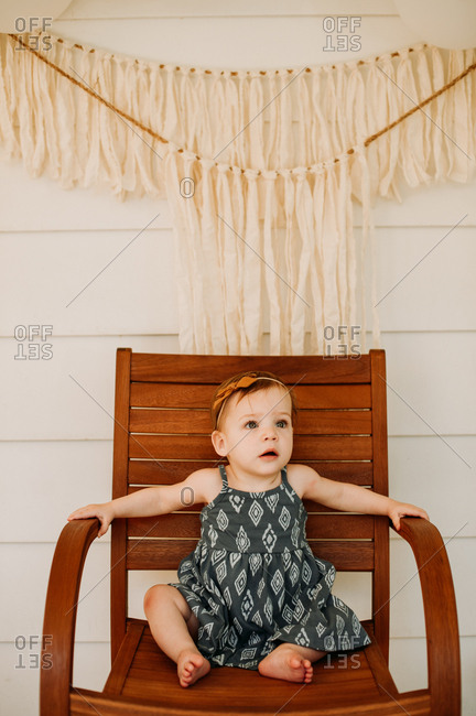 Portrait of a baby girl with brown bow sitting on wooden chair
