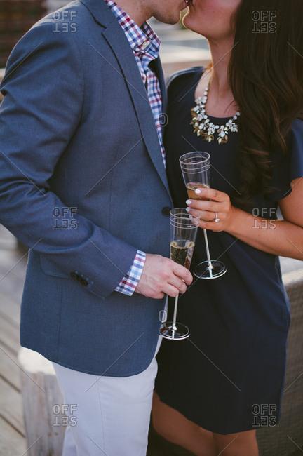 Couple kissing while enjoying champagne as engagement celebration