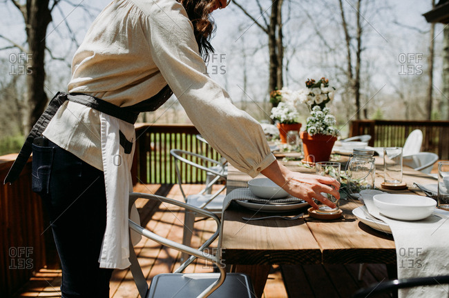 Woman setting table for brunch on a deck table