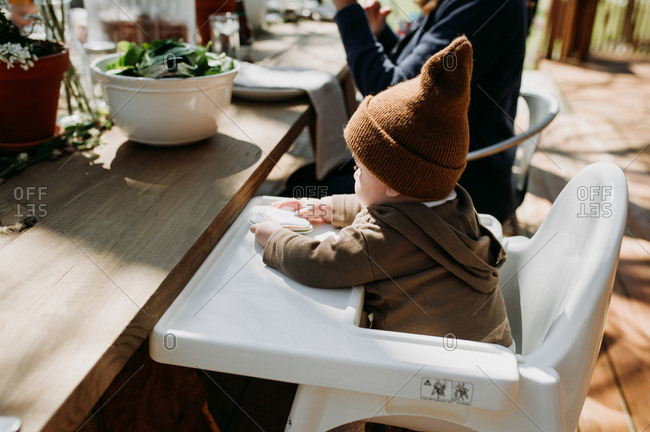 Baby sitting at highchair on an outdoor deck