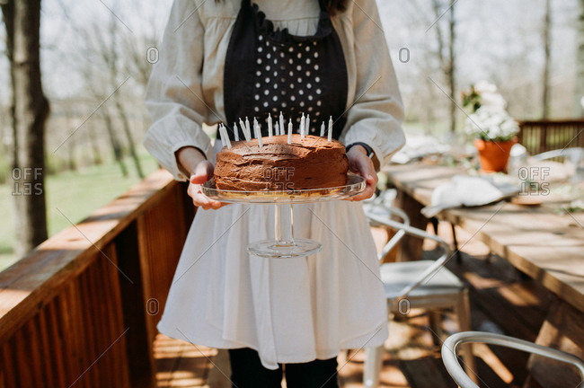 Woman holding birthday cake on a deck table
