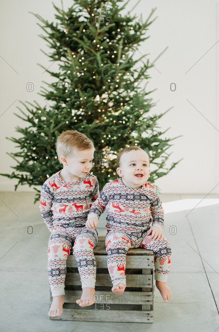Two boys in pajamas in front of a Christmas tree