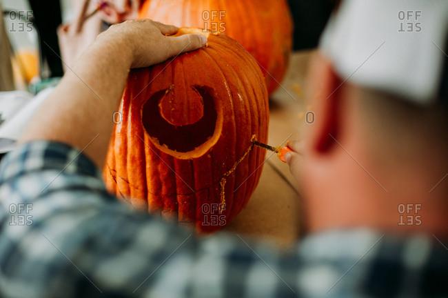 Man carving pumpkin for Halloween
