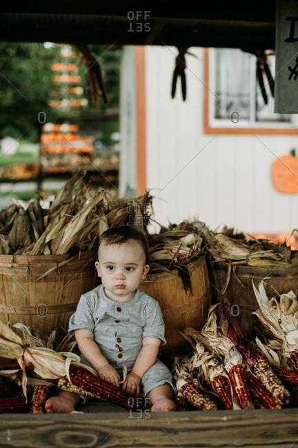 Baby sitting by baskets of flint corn