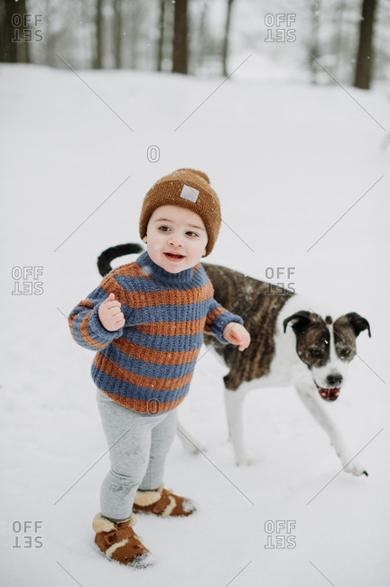 Baby boy playing in the snow with dog