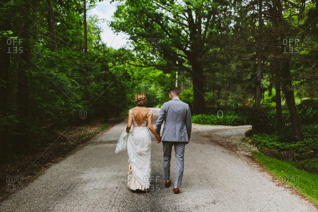 Rear view of bride and groom walking on rural path