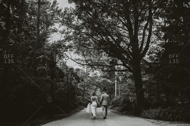 Rear view of bride and groom walking on rural path in black and white