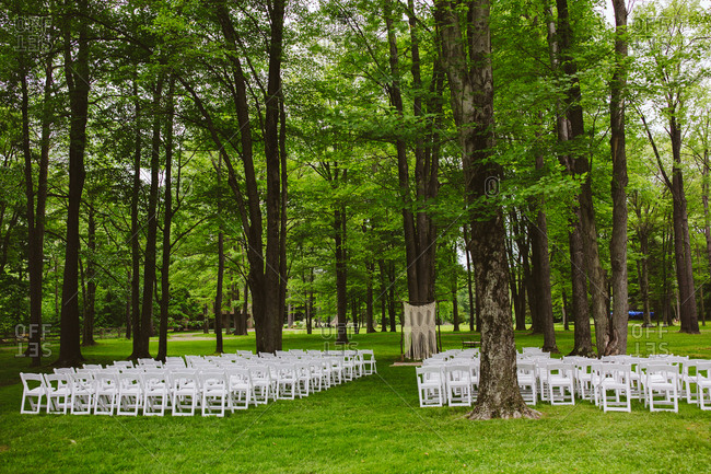 White chairs set up by trees in a rural wedding