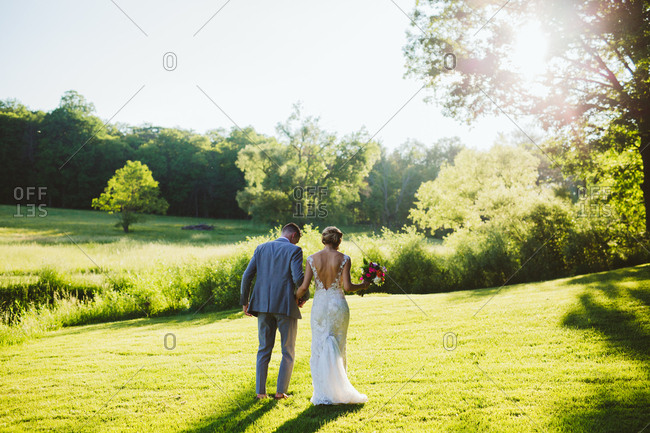 Rear view of bride and groom walking in the sunny countryside