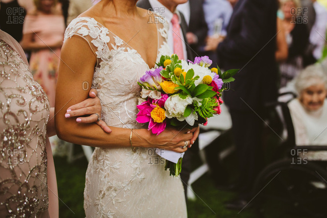 Bride holding colorful bouquet walking own aisle with mother