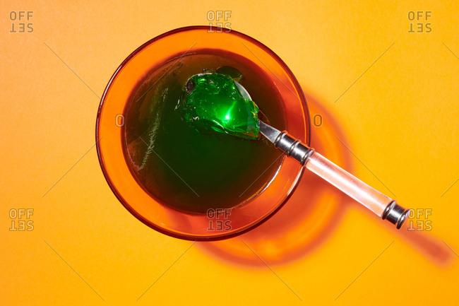 Green lime flavored gelatin dessert in orange serving glasses on orange background