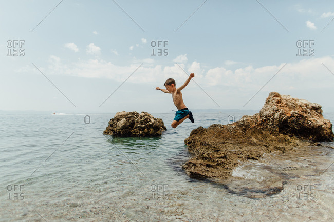 Child jumping off rocks into the sea.