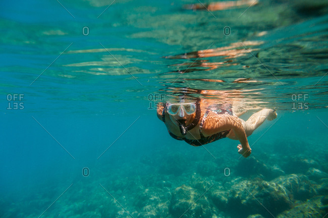 Female swimmer wearing mask and snorkel diving in sea over rocky bottom.
