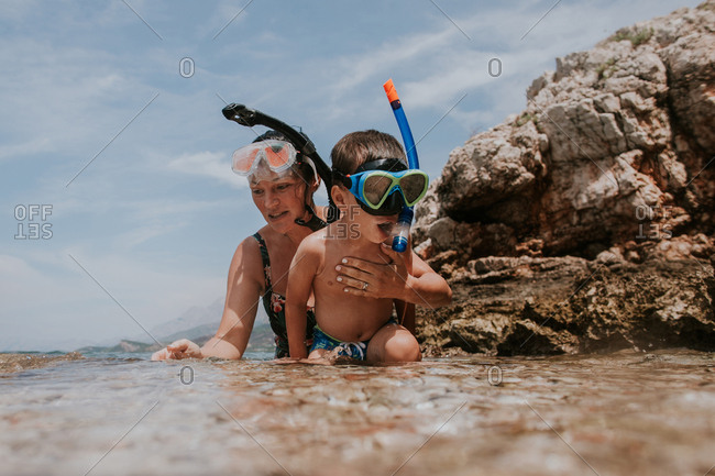 Woman and child learning to snorkel in the sea.