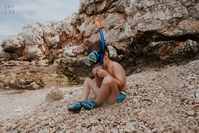 Child sitting on beach putting on snorkeling mask.