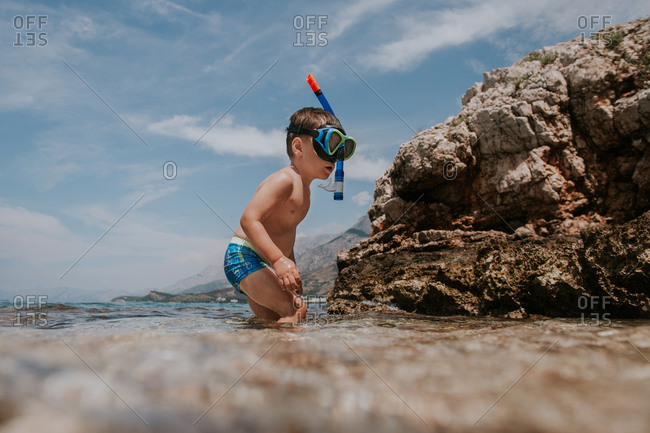 Child with diving mask and snorkel walking out of water.