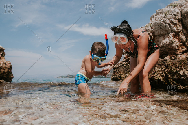 Child exploring sea with his mother.