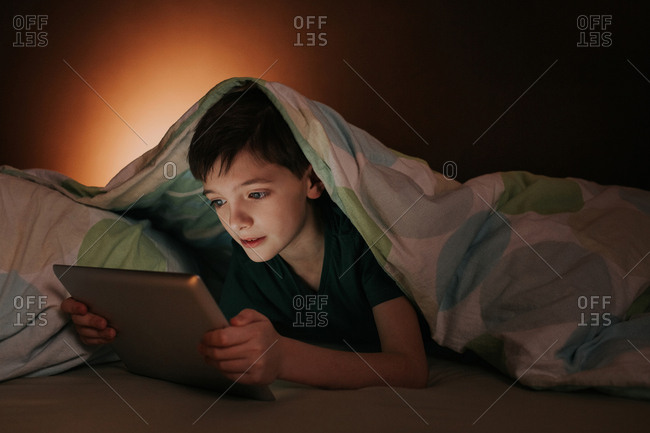 Young boy covered with duvet playing games on tablet.