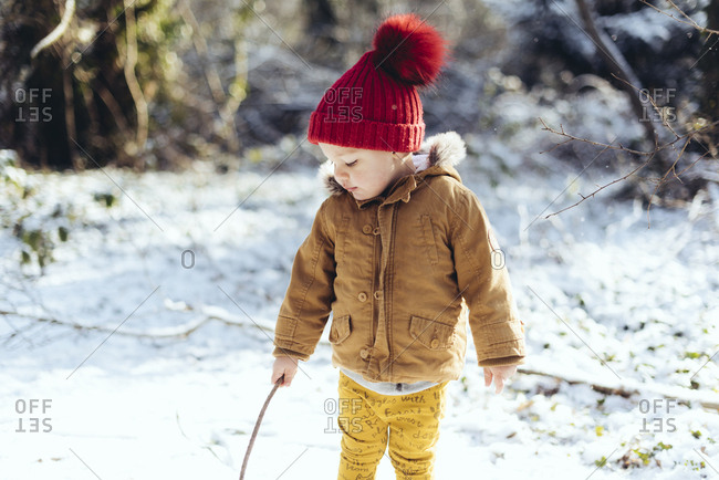 Boy playing with a twig in snow