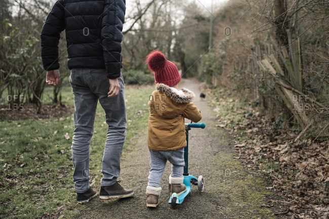 Young boy scooting with his father