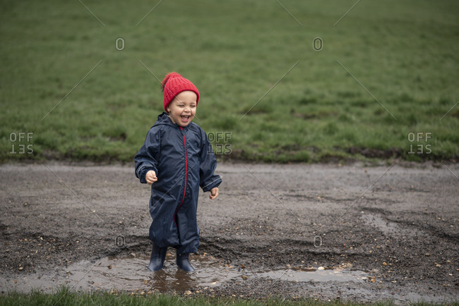 Happy boy in a mud puddle on a road