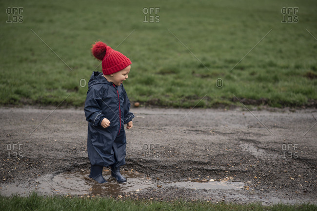 Boy full of joy in a mud puddle on a road