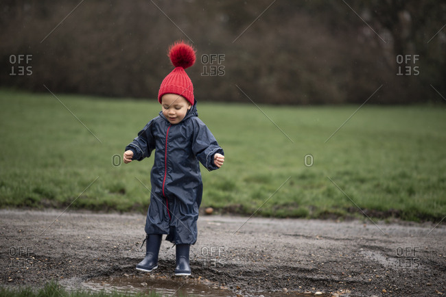 Boy jumping in a mud puddle on a road