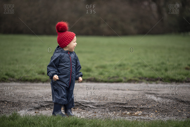 Boy jumping in a mud puddle on a road in the rain