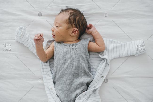 Newborn baby boy on bed being dressed