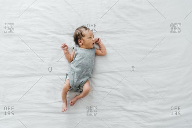 Newborn baby boy on bed in gray onesie