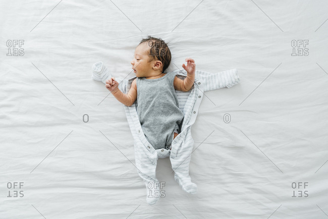 Overhead view of newborn baby boy on bed being dressed