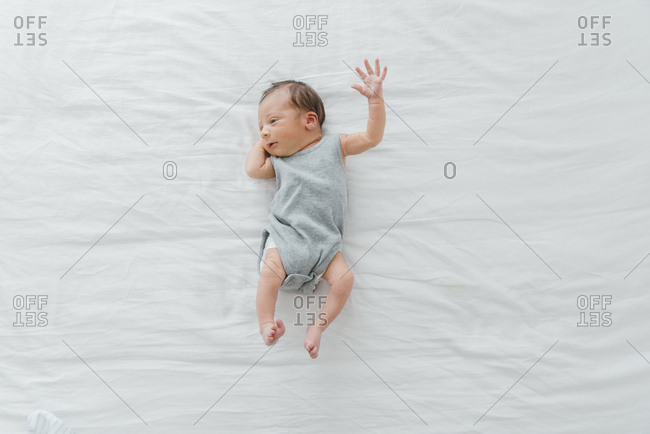 Newborn baby on bed in gray onesie