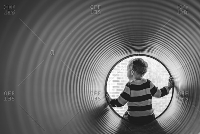 Boy sitting at the end of a tunnel