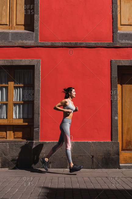Side view of sportswoman jogging at red building on sunny city street