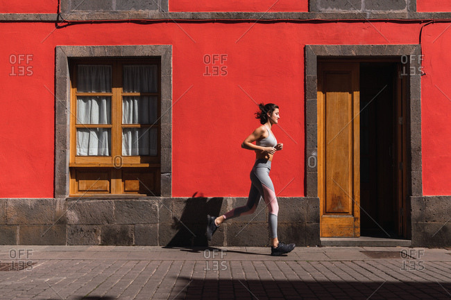 Side view of young jogging sportswoman moving on city street at red building