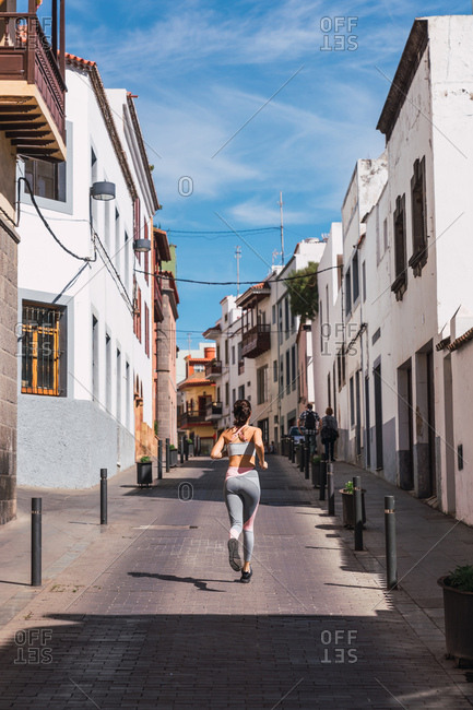 Back view of athletic sportswoman running up on hill on sunny street