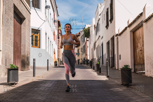 Athletic sporty woman in gray clothes running down the hill on sunny street in town